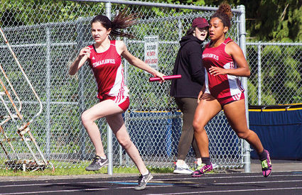 Marysville-Pilchuck's Olivia Lee, right, hands off to Lily Shields, left, during the 4x200-meter relay at Arlington High School on May 9. - Andrew Hines, North County Outlook