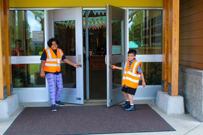 Photo of students welcoming guests and opening the door for them