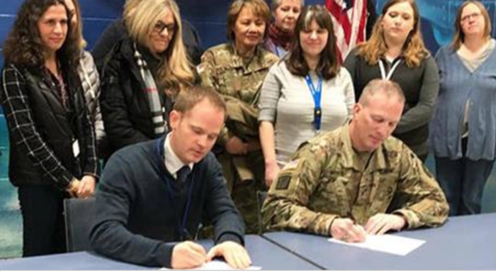 Photo of Principal Taylor Signing Document with Army Reserve